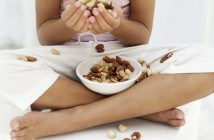 Young Girl (8-9) Holding Nuts in Her Hands and a Bowl of Nuts on Her Lap