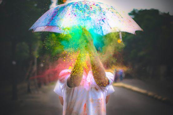 Una persona di cui non vediamo la faccia sta battendo le mani e dal battito scoppiano polveri colorate: gialle, verdi, azzurre, rosse. Sulla sua testa un ombrello bianco, che però è cosparso di altre polveri colorate, blu e viola.