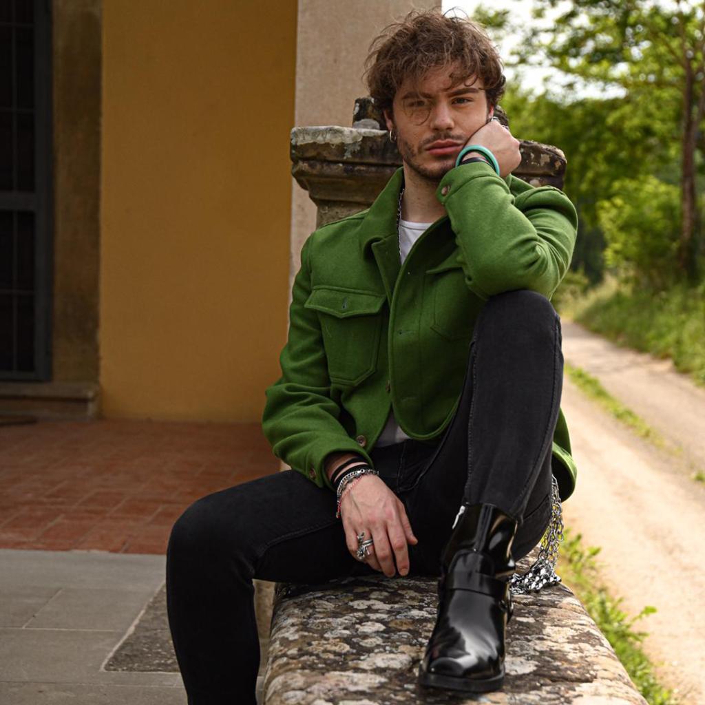 Luca Gremita, seduto su un muretto, indossa una giacca verde e dei pantaloni neri.