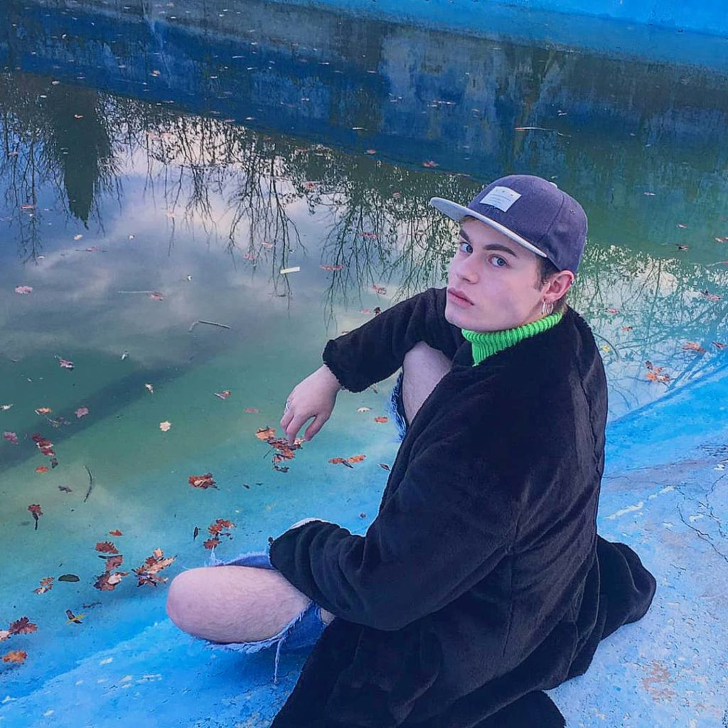 Luca Gremita, seduto sul bordo di uno specchio d'acqua, indossa un lungo cappotto nero. L'immagine è tutta sui toni dell'azzurro.