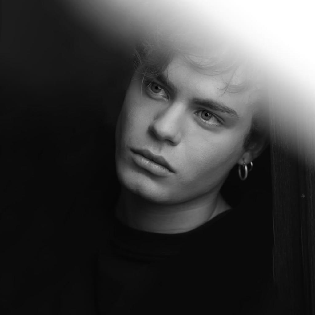 Luca Gremita a mezzo busto, in bianco e nero, con un fascio di luce che riempie la parte in alto a destra dell'immagine.